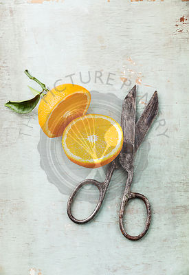 Ripe orange with leaf and vintage scissors on textured background