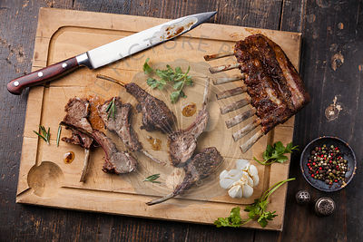 Roasted lamb ribs and kitchen knife on wooden cutting board on dark background