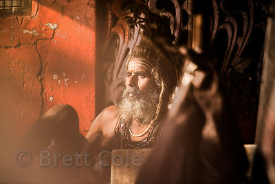 A sadhu enveloped in tobacco smoke at the Brahma temple, Pushkar, Rajasthan, India