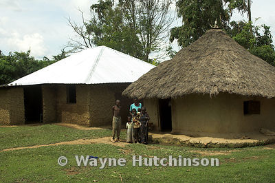 Two mud huts with family outside one with thatched roof and one with tin roof, built with procedes from a charity donated cow...