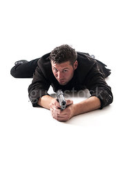 A mystery man in big coat, laying on the floor and pointing a gun – shot from low level.