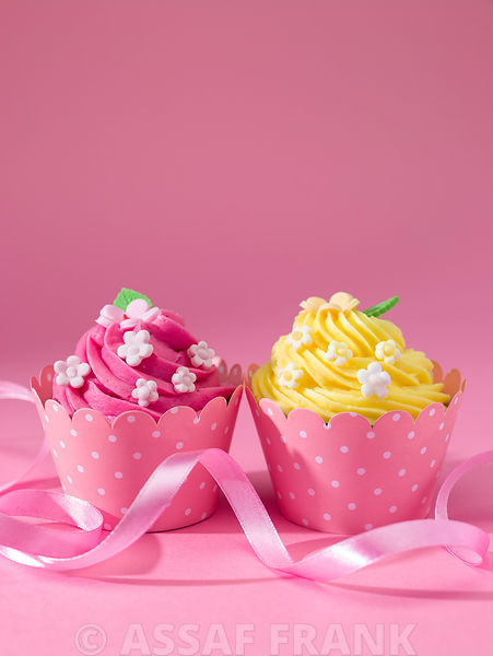 Beautifully decorated cupcakes on pink background