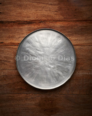 Aluminum pizza shape, empty and worn on wooden background