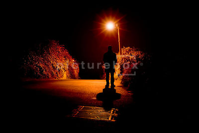 An atmospheric image of a man standing in a country lane at night, lit by a single streetlight.