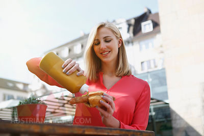 Smiling blond woman with fried sausage outdoors