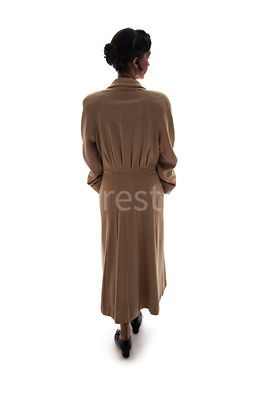 A semi-silhouette of a vintage 1920s - 1930s woman in a coat – shot from eye level.