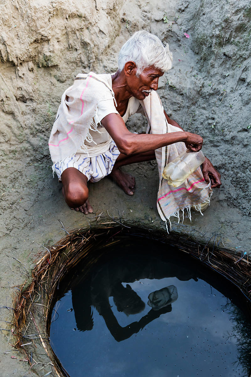 Man Filtering Water Drawn from a Homemade well in the Yamuna River Flood Plain