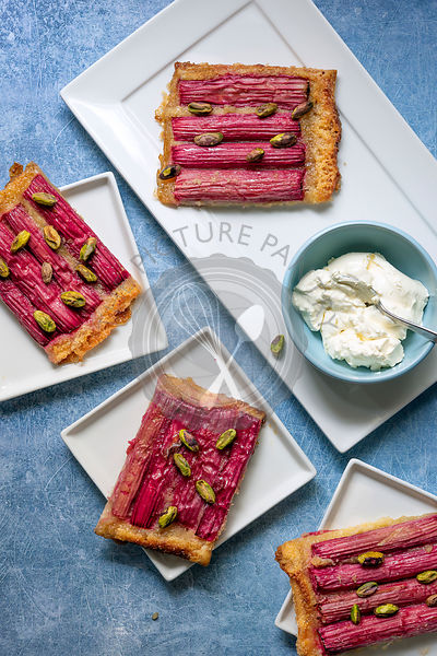 Servings of rhubarb tart sprinkled with pistachio nuts on dessert plates with a bowl of cream.