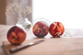 White nectarines on a cutting board with white flowers. Light, brught, summery background.