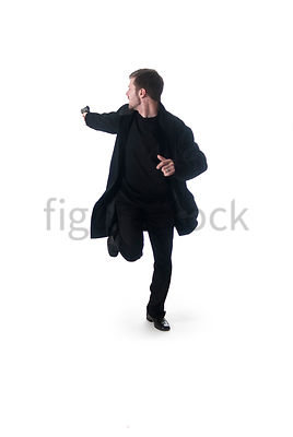 A Figurestock image of a man with a gun, running and looking over his shoulder – shot from eye level.