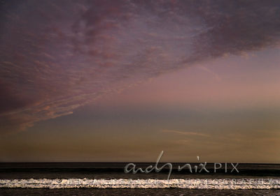 White foam from a wave breaking in a straight line under a dark dusky pink and ochre sky.