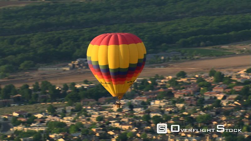 Close flight tracking hot air balloon floating over Albuquerque suburbs near Rio Grande.