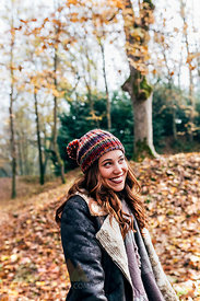 Portrait of a beautiful happy woman in an autumnal forest