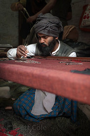 An artist works on a needlepoint tapestry or rug, Varanasi, India.