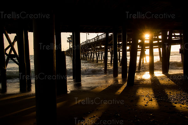 The setting sun behind the pillars holding up the pier cast long shadows