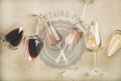 Red, rose and white wine in glasses over grey background