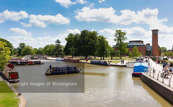 Canal boats mooring alongside the River Avon at Stratford upon Avon, the Royal Shakespeare Theatre is to the rear.
