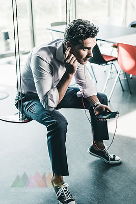 Businessman in office sitting on swing, using smartphone