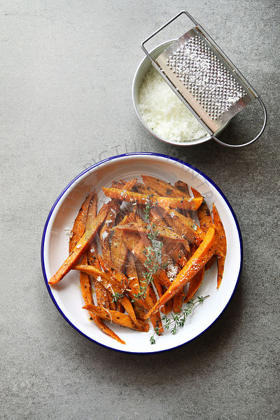 Sweet potatoes fries in an enamel plate  with grated parmesan,spices and thyme