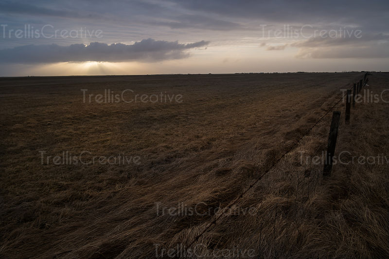 Sunbeams shine down in the distance from barren farmland in Iceland.