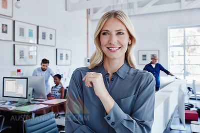 Smiling businesswoman in office with staff in background