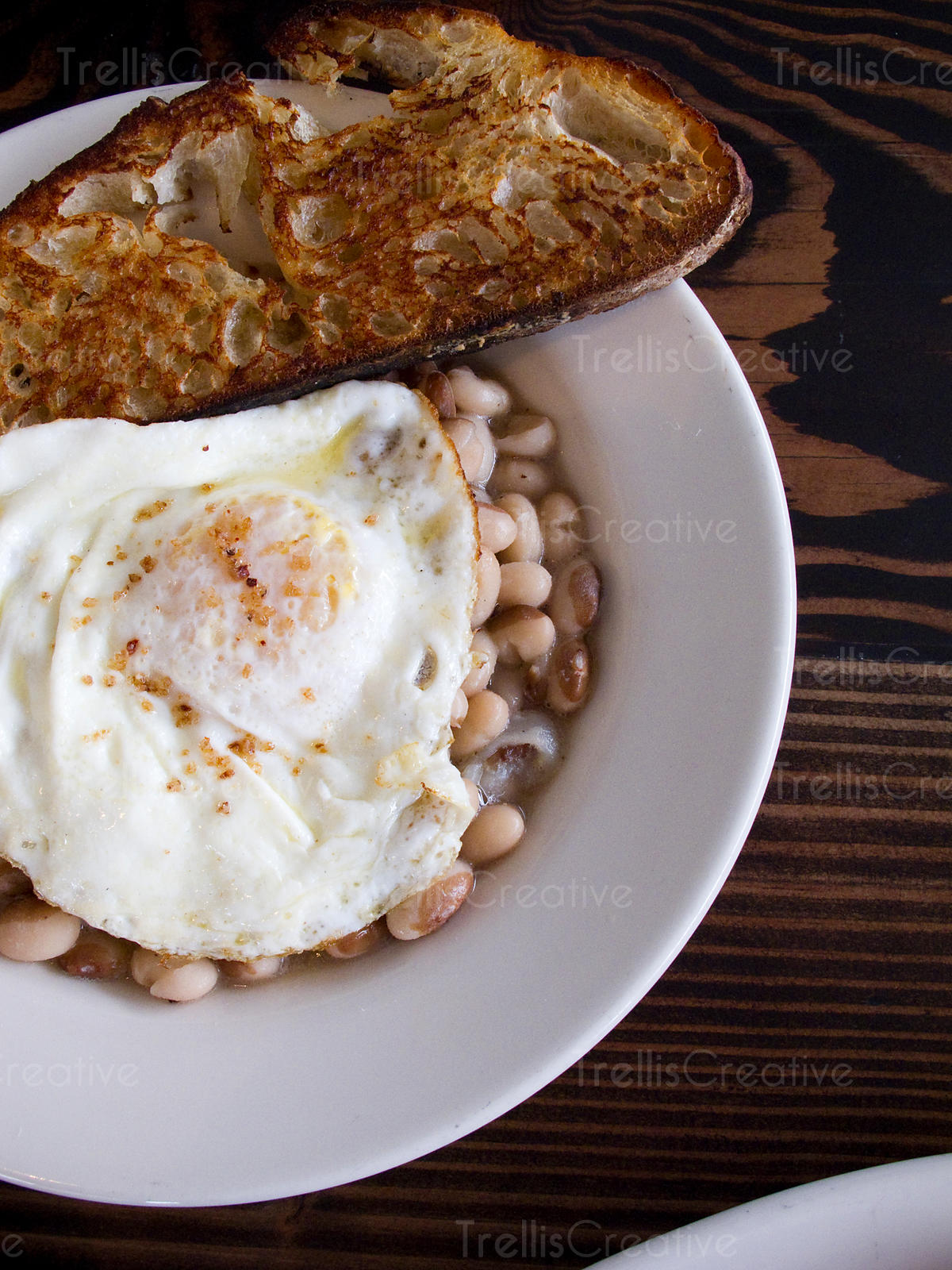 Fried egg over a bowl of white beans