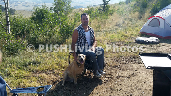 Man using a wheelchair camping with his dog