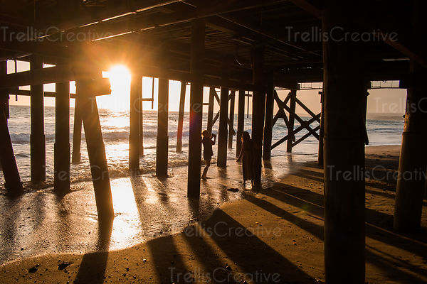 People taking photographs under the pier at sunset