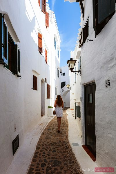 Woman walking in an alley, Binibeca Vell, Spain