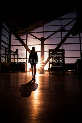 A silhouette of a lone woman walking through an empty airport or office building.