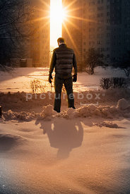 An atmospheric image of a lone mystery man standing in the snow with the sun shining between two blocks of flats.