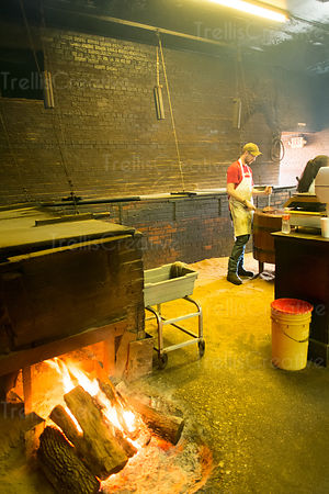 Chef preparing food in barbecue smokehouse in Lockhart, Texas
