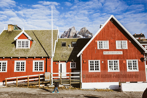 A child walks by a red wooden building in Uummannaq, Greenland