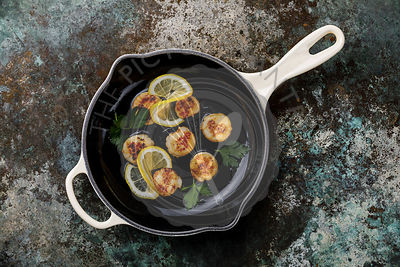 Fried scallops with butter in cast-iron cooking pan with lemon and leaf vegetable