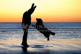 Silouhette of dog and handler on the beach at sunrise