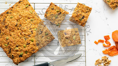Apricot, pumpkin seed and oatmeal slice cut into pieces, cooling on a wire rack with of dried apricots and walnuts.