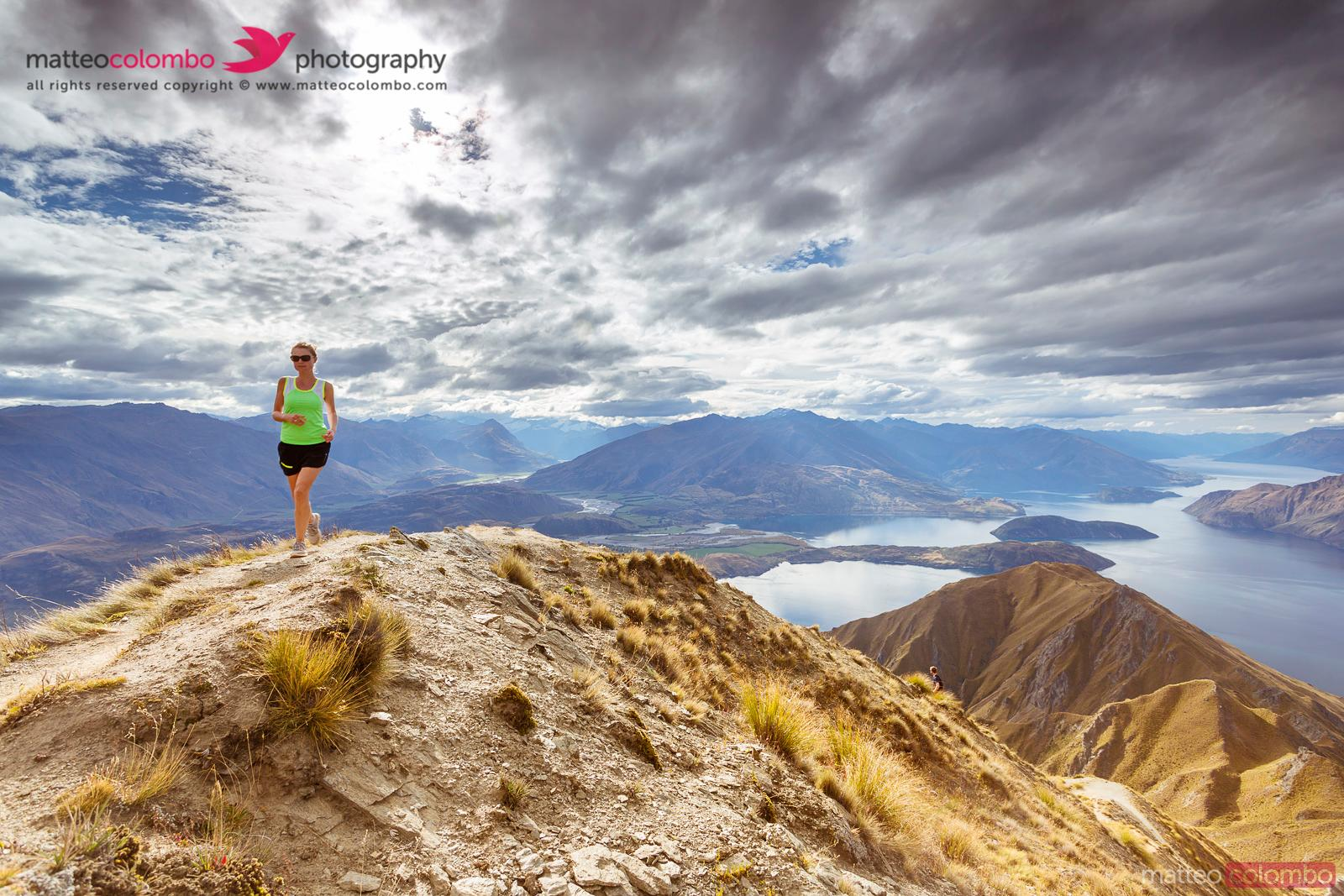 Woman running on the crest of mountain, New Zealand