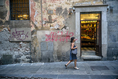 A Woman Walks Past A Grocers shop In The Old Centre Of Genoa