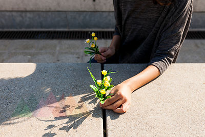 Close-up of woman holding yellow flower on concrete