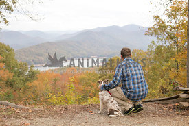 man and his dog looking out at the beautiful fall landscape