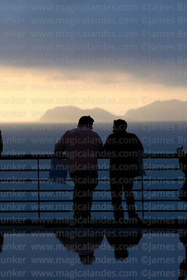 Men chatting as they watch sunset from Larcomar, La Punta headland in background, Miraflores, Lima, Peru