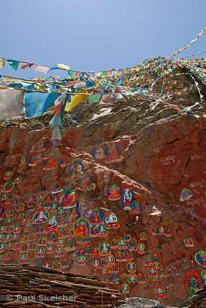 Painted rock carvings of revered Buddhist figures along the prayer-flag lined walkway up Chagpo Ri mountain, part of the sacr...