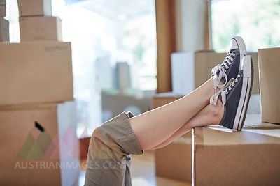 Couple moving house, woman's feet on a box
