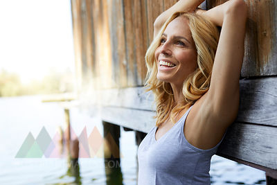 Happy blond woman leaning against wooden hut at a lake