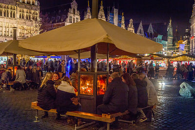Shoppers relaxing round a wood burner at one of Antwerp's many Christmas Markets