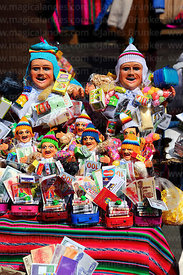 Ekekos and miniature suitcases with travel documents for sale on market stall, Alasitas festival, La Paz, Bolivia