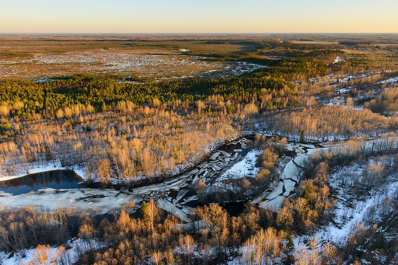 Aerial view of ice breaking in Halliste river, with Kuresoo bog in the background.  Soomaa National Park, Viljandimaa County....