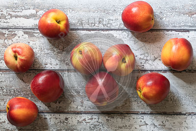 Red and yellow nectarines on wooden boards.