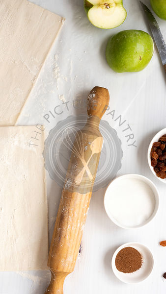 Ingredients for apple studel, including pastry, sugar, cinnamon, apples, sultanas and a rolling pin.