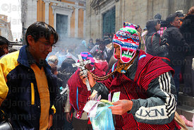 A yatiri or shaman blesses miniature banknotes with a silver crucifix, Alasitas festival, La Paz, Bolivia